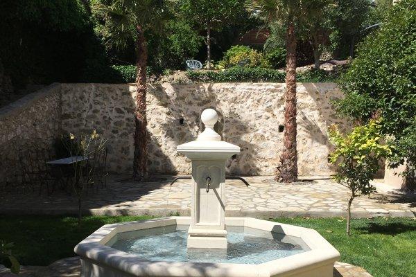 Fontaine centrale en pierre de d'Estaillade finition égrisée.  4 sorties d'eau